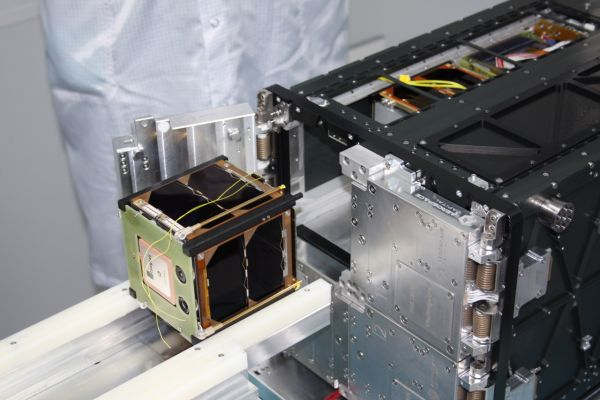 Na snímku se družice právě umísťuje do takzvaného deployera, vypouštěče, ze kterého jsou CubeSaty pružinami uvolněné na oběžné dráze do vesmíru.